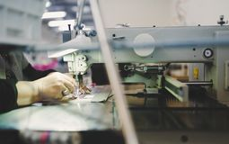 Worker in textile industry sewing stock image