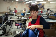Worker in textile industry sewing stock photography