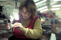 Worker in textile industry sewing stock photo