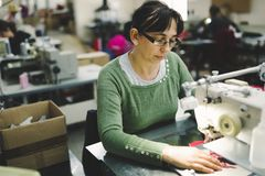 Worker in textile industry sewing royalty free stock images