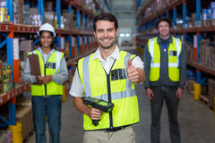 Worker with thumb up wearing yellow safety vest. Worker in warehouse with thumb up wearing yellow safety vest Royalty Free Stock Image