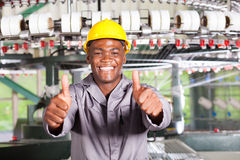 Worker thumbs up. African american textile worker thumbs up in front of weaving loom Royalty Free Stock Images