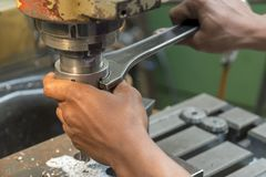 The worker tighten  the nut of  the tool holder. Of milling machine Royalty Free Stock Image