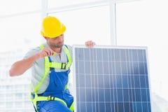 Worker tightening solar panel in office Stock Photo