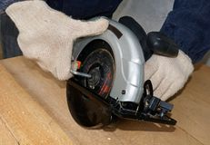 The worker tightens the blade. Setting the blade of the circular saw Stock Photo
