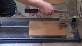 Worker tiler man use tile cut tool on floor. Left side sliding stock footage