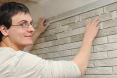 Worker tiler at wall decoration Stock Photos