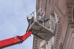 Worker to lift platforms, control facades Royalty Free Stock Photo