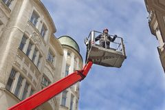 Worker to lift platforms, control facades Stock Photography