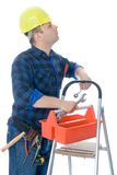 Worker and tool-box. Worker (handyman) is checking his tools in tool-box on ladder and looking up Stock Image