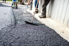 Worker with tool working with fresh asphalt and bi Royalty Free Stock Images