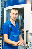 Worker at tool workshop. Mechanical technician near cnc milling machine center at tool workshop Royalty Free Stock Photo