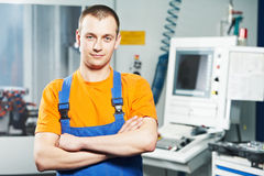 Worker at tool workshop. Mechanical technician near cnc milling machine center at tool workshop Royalty Free Stock Photography