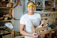 Worker with toolbox. Happy female worker with wooden toolbox wearing protective eyeglasses during work Royalty Free Stock Images
