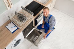 Worker With Toolbox Repairing Dishwasher Royalty Free Stock Images