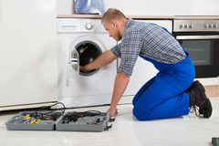 Worker With Toolbox Repairing Washing Machine Stock Photos