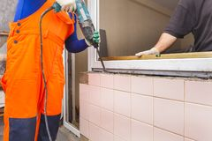 The worker installs plastic windows and doors. The worker tools installs plastic windows and doors stock images