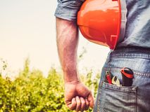 Worker with tools and an orange helmet. Standing against a background of green trees and blue sky. Rear view, close-up. Concept of work and employment Stock Photo