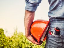 Worker with tools and an orange helmet. Standing against a background of green trees and blue sky. Rear view, close-up. Concept of work and employment Stock Photography
