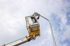 Worker on top of a pole fixing the supply 3 Stock Photo