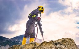 Worker on top of a rock. Worker with helmet and protective suit using a drilling machine on top of a large rock Stock Photography