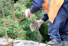 Worker touches the crane hooks to the loops in the concrete slab during repair work. Royalty Free Stock Photography
