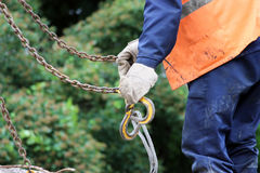 Worker touches the crane hooks to the loops in the concrete slab during repair work. Royalty Free Stock Image