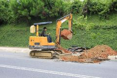 Worker  tracked excavator on the street asphalt  for road repairing Stock Photography