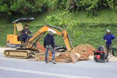 Worker  tracked excavator on the street asphalt  for road repairing Stock Image
