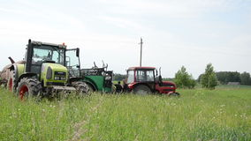 Worker tractor heavy. Two workers stand on the two heavy field work tractors talk about the field sprayers circa June 2013 in Birzai, Lithuania stock video