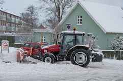 Worker on a tractor with a snow plow plowing snow Royalty Free Stock Image