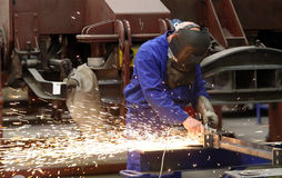 Worker in train factory. Worker cuttin metal at train factory in Croatia Royalty Free Stock Photo
