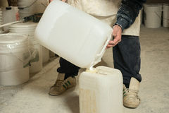 Worker Transfering Liquid Plaster Resin into Plastic Container Stock Photo