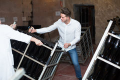 Worker transporting bottles of wine at sparkling wine industry. Male worker transporting bottles of wine to storage at sparkling wine industry Stock Photos