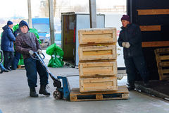 Worker transporting wooden boxes on a hand trolley. Stock Photos