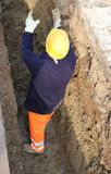 Worker in the trench. With yellow hardhat Royalty Free Stock Images