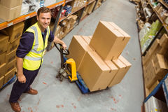 Worker with trolley of boxes smiling at camera Stock Image