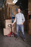 Worker with trolley of boxes in warehouse Stock Images
