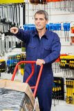Worker With Trolley Pointing In Hardware Shop Royalty Free Stock Image
