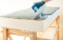 Worker with trowel covering foam plastic Royalty Free Stock Photo