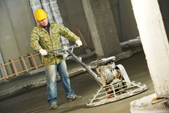 Worker trowelling and finishing of concrete. By special construction equipmant Royalty Free Stock Photo