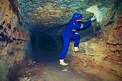Worker in tunnel. Staff  in a protective suit check sediments in rocky wall Stock Image