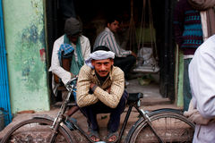 Worker in a turban rests leaning on his retro bicycle on the street royalty free stock images