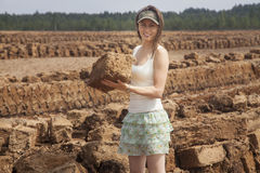 Worker at peat field. Worker at turf field holding cut peat block stock photo