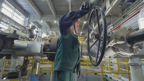 Worker Turns Round Metal Lever on Gas Pipeline. KAZAN, TATARSTAN/RUSSIA - SEPTEMBER 19 2017: Side view skilled worker in helmet turns round large black metal stock video