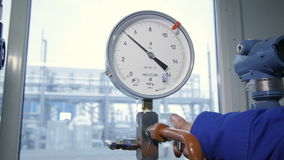 Worker Turns Steel Valve in Meter Control Gouge. Closeup worker in blue uniform turns steel valve in meter control gouge in big plant background out window stock footage