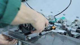 Worker twisting industrial unit to metal basis. Manual assembly at factory