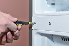Worker twists the screw with a screwdriver. Closeup Royalty Free Stock Images