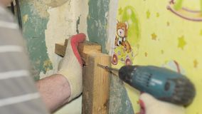 Worker twists the into wooden Board electric screwdriver, home renovations stock footage