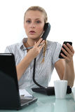 Worker with two phones Royalty Free Stock Photography